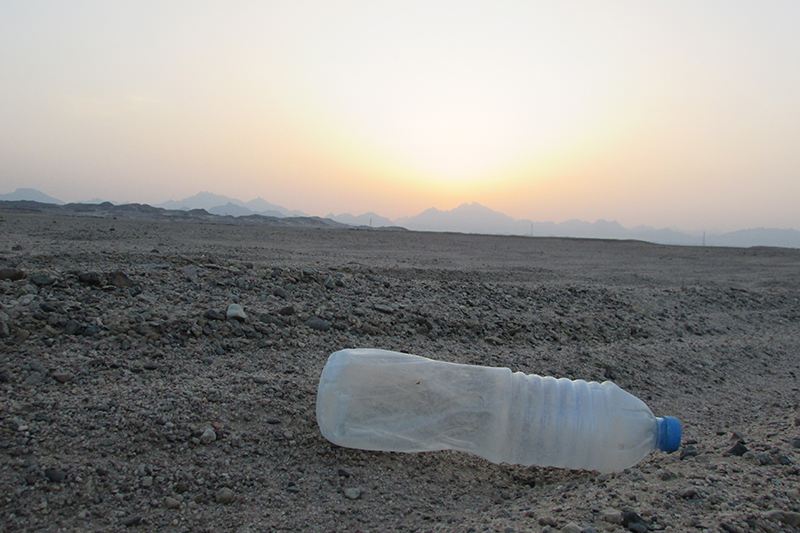 An image of a discarded plastic bottle on a beach.
